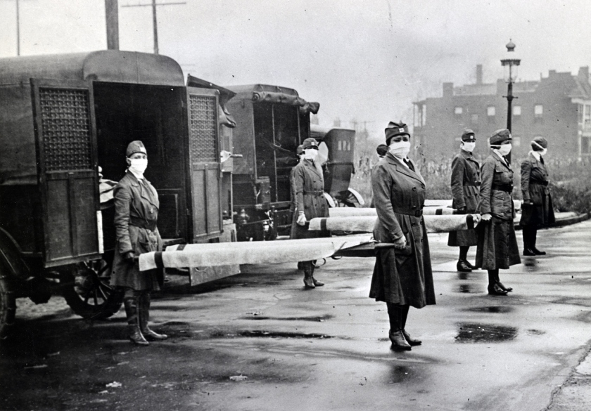St. Louis, (Missouri) Red Cross Motor Corps on duty during the Spanish Influenza epidemic, 1918. Photograph shows mask-wearing woman holding stretchers at backs of ambulances.